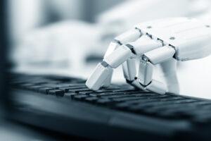 Symbolbild Textautomatisierung: Eine Computerhand tippt auf einer Tastatur.