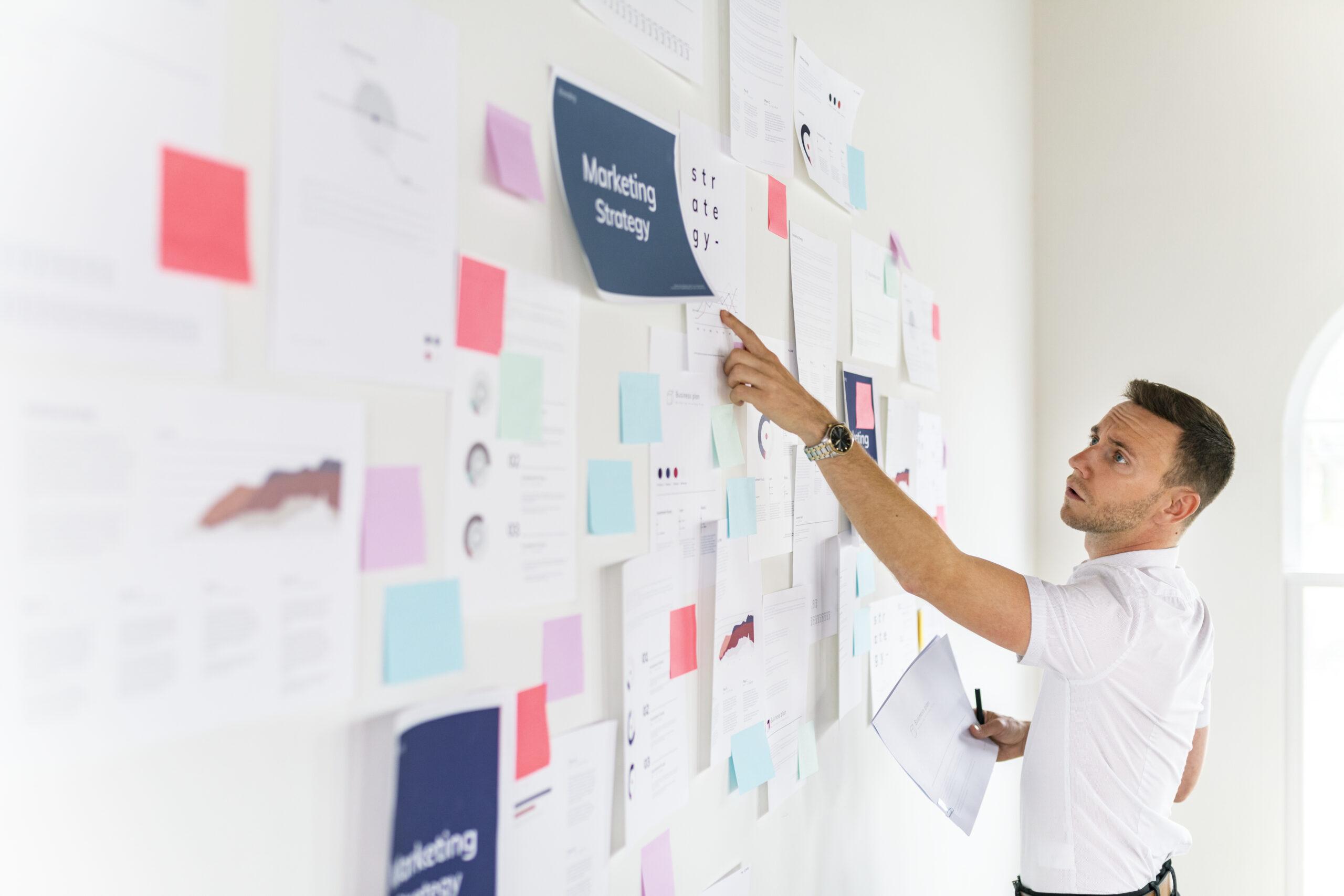 Mann steht vor einem Strategy-Board